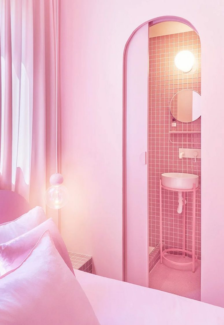 The bathroom is clad with pink tiles, and you may see a small round mirror and a sink on a stand