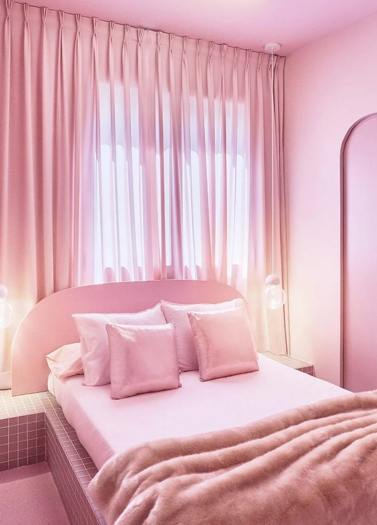 The bedroom is done in pink, with a pink bed on a tiled platform, pink and shiny pillows, a pink curtain and lights