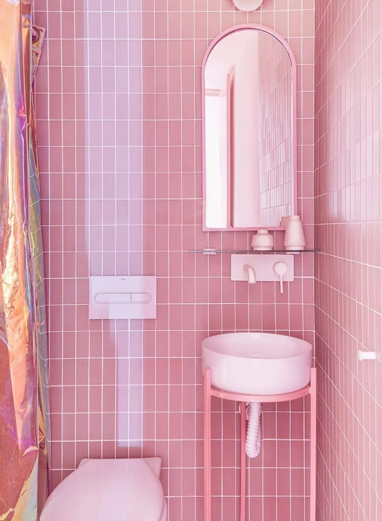 There's also another bathroom clad with pink tiles, a round sink and an arched mirror plus a shower space