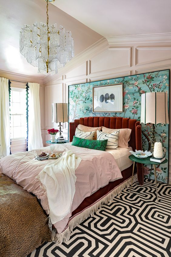 a colorful vintage bedroom with paneling, a bright floral wall, a burgundy bed, colorful bedding and a crystal chandelier