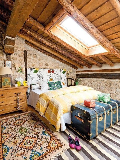 a catchy and colorful vintage attic bedroom with a floral bed, bold bedidng and rugs, a vintage blue chest and stone walls