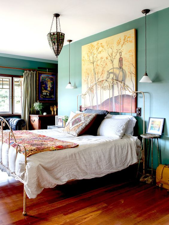 a bold and whimsy vintage bedroom with green walls, a metal bed, colorful bedding, bold artworks and a stained glass chandelier