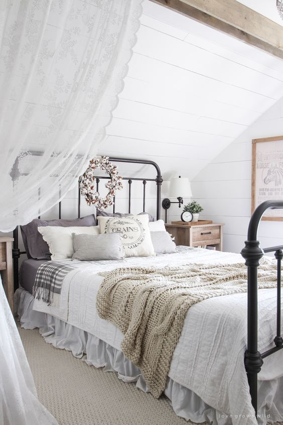 a neutral attic bedroom with a vintage and farmhouse feel, a metal bed, neutral and printed bedding, lace curtains and greenery