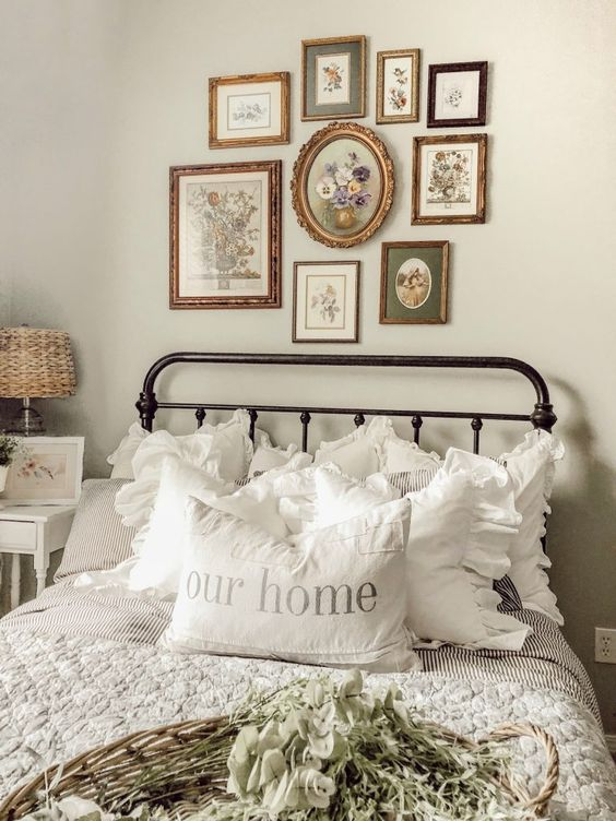 a beautiful and cozy vintage bedroom in neutrals, with a metal bed, a chic gallery wall, printed bedding and white nightstands