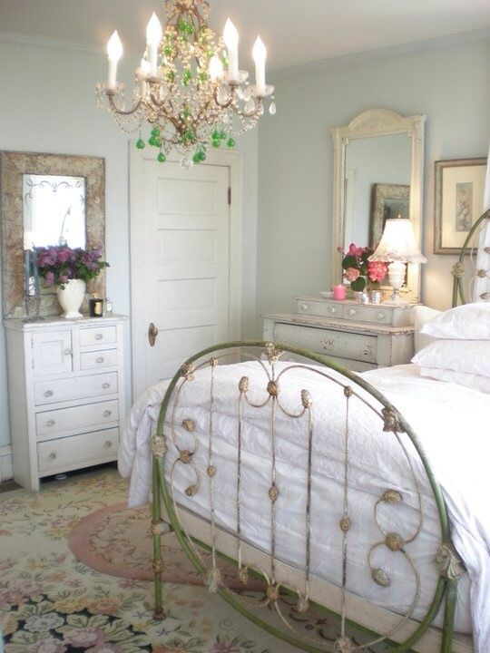 a neutral and pastel vintage bedroom with a metal bed, a crystal chandelier, mirrors and a chic floral rug