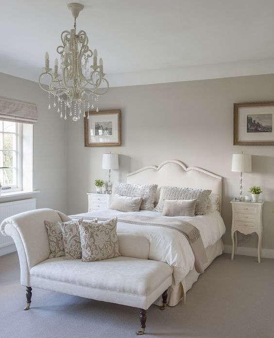 a chic neutral vintage bedroom with dove grey walls, creamy furniture, a crystal chandelier and printed textiles