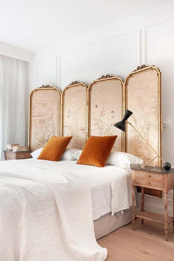 a refined vintage bedroom with a framed fabric screen, rust pillows, a statement lamp and wooden nightstands