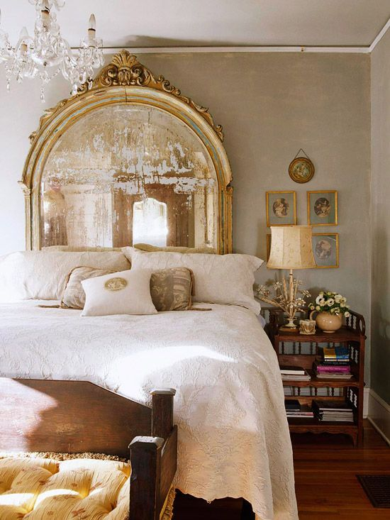 a vintage bedroom with neutral walls, a vintage mirror as a headboard, a crystal chandelier and a chic gallery wall