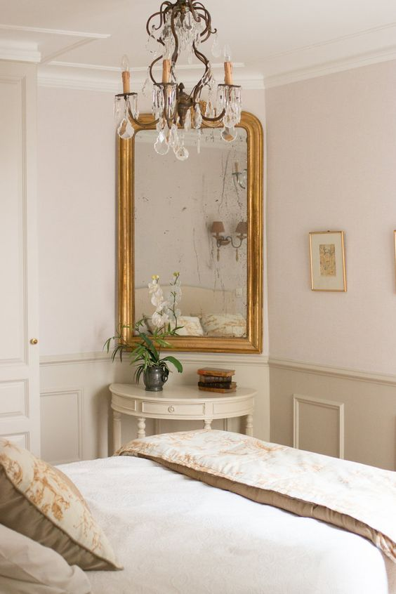 a sophisticated neutral bedroom with paneling, a vintage mirror, a crystal chandelier and chic bedding