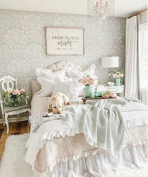 a pastel vintage bedroom with a printed wallpaper wall, a refined bed and nightstands, printed bedding and a crystal chandelier