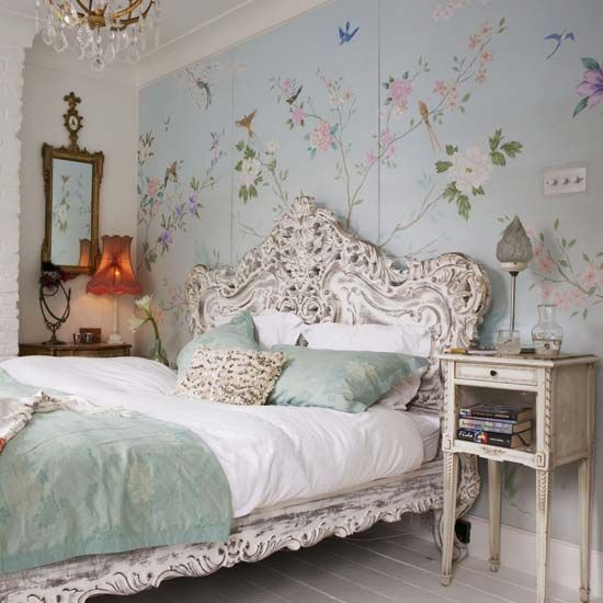 a refined vintage bedroom with a floral statement wall, refined shabby chic and vintage furniture, a crystal chandelier, a mirror and a lamp