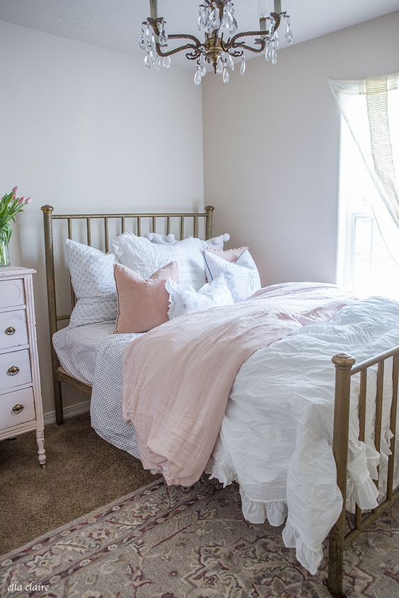 a neutral bedroom with a metal bed, a crystal chandelier, a blush sideboard and blush and white bedding