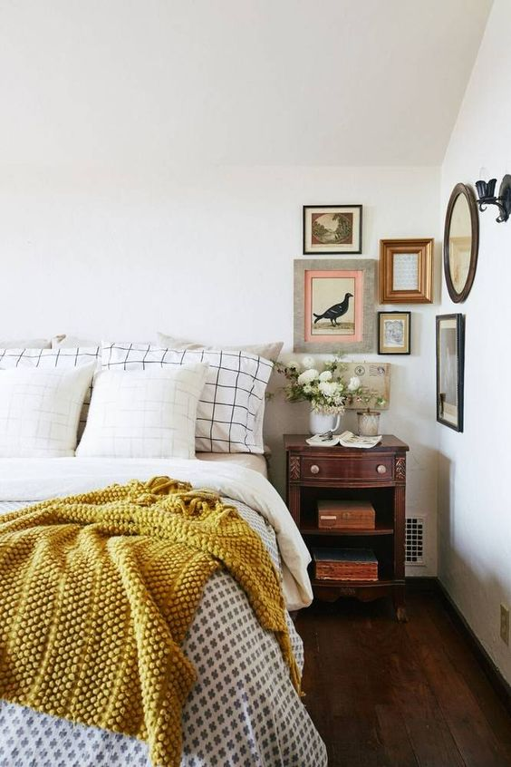 a retro bedroom with neutral walls, heavy and dark furniture, a gallery wall and white blooms is very chic