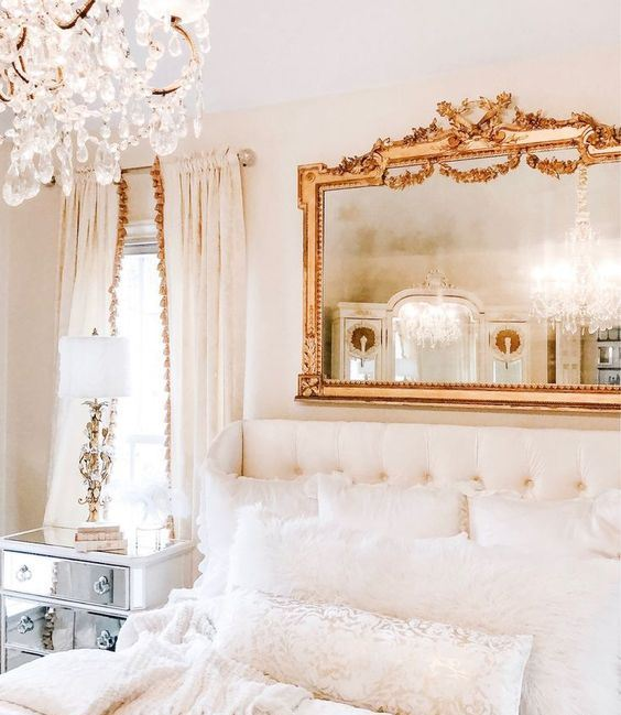 a refined neutral bedroom with a mirror in a chic frame, a crystal chandelier and a gorgeous upholstered bed
