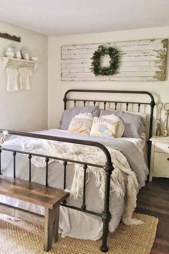 a neutral bedroom in vintage and shabby chic style, with a wooden artwork and a wreath, a forged bed, striped bedding and some neutral decor
