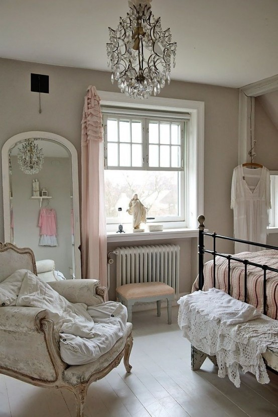 a refined vintage bedroom with grey walls, elegant furniture, a forged bed, a refined neutral chair and a crystal chandelier