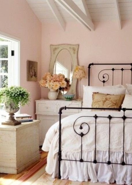 a blush vintage bedroom with neutral furniture, a forged bed, a mirror and some greenery and dried bloom arrangements