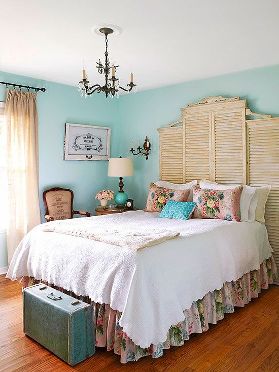 a bedroom with turquoise walls, chic vintage furniture, shutters at the headboard, a vintage chandelier and neutral and floral bedding