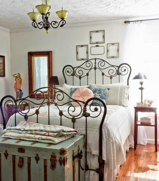 a vintage bedroom with white walls, vintage furniture and a forged bed, a mint chest at the foot and a gallery wall