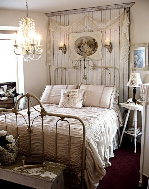 a vintage to shabby chic bedroom in neutrals, with a wooden statement wall, a forged bed, vintage furniture, a crystal chandelier