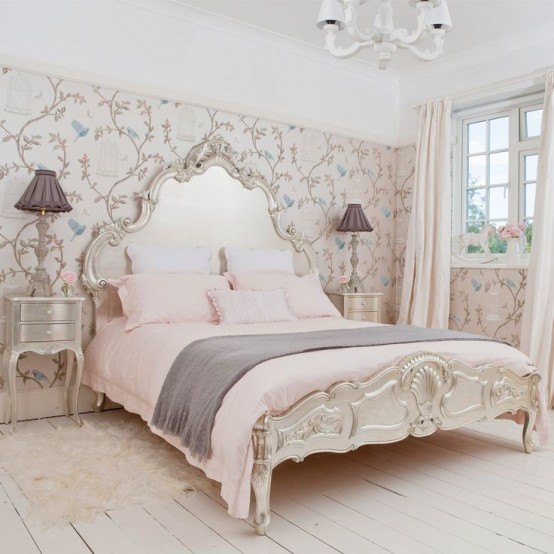 a pastel and neutral vintage bedroom with a floral wallpaper wall, refined vintage furniture, a chic chandelier and grey and pink bedding