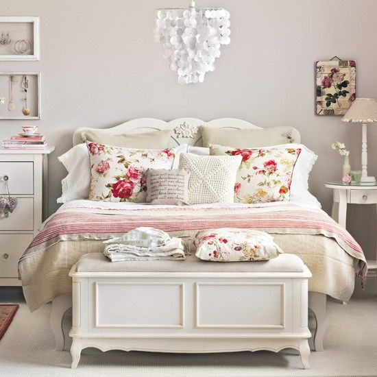 a romantic neutral bedroom with grey walls, white furniture in vintage style, a shell chandelier and floral bedding for a romantic feel