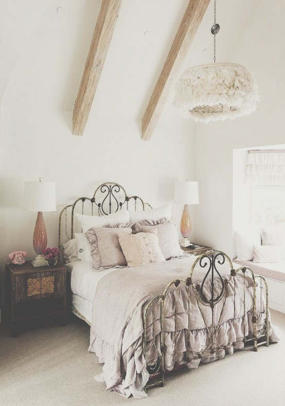 a neutral vintage bedroom with wooden beams, a forged bed with grey and white bedding with ruffles and chic nightstands