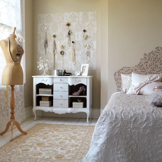 a neutral and glam vintage bedroom with warm-colored walls, a bed upholstered with floral fabric, a rug and curtains in florals, a jewelry stand with accessories