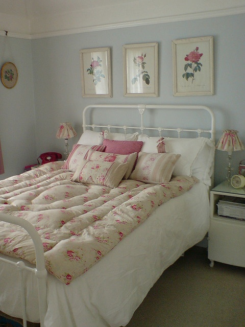 a vintage pastel bedroom with light blue walls, a metal bed and vintage furniture, floral artworks and floral bedding for a cute touch