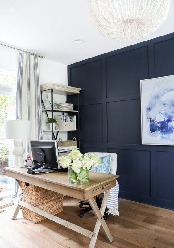 a modern farmhouse home office with a navy statement wall, a wooden trestle desk, a white chair and a basket