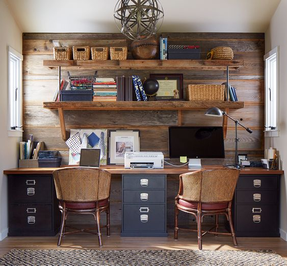 a rustic home office with a salvaged wooden wall, a shared desk, woven chairs and an open shelving unit