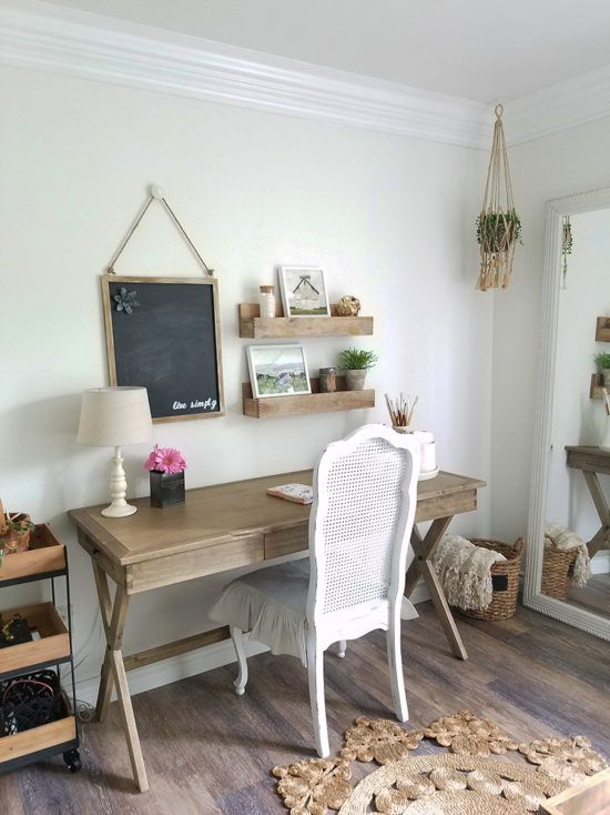 a neutral farmhouse home office with a wooden trestle desk, a white chair, a jute rug and wooden shelves