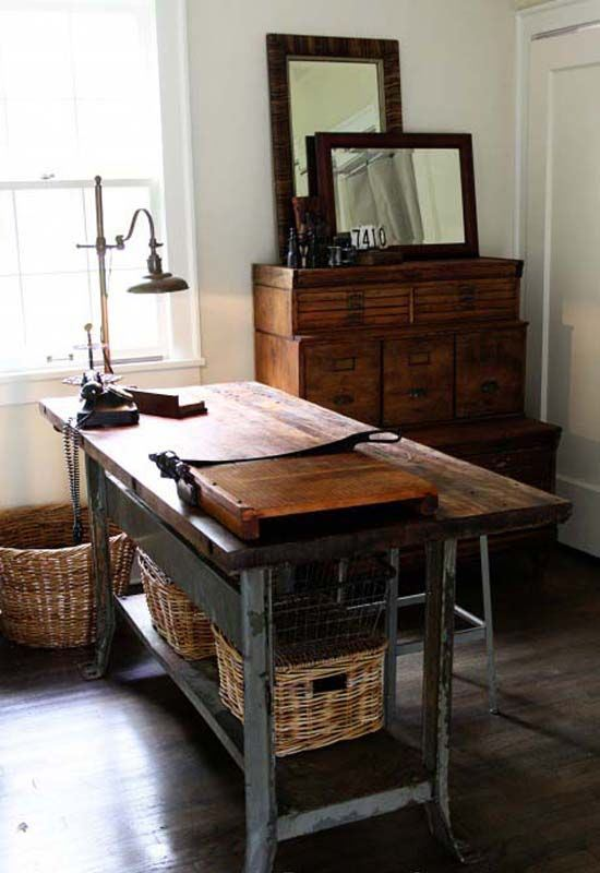 a rustic home office with a wood and metal desk, baskets, a vintage sideboard and mirrors is very chic