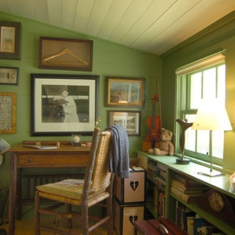 a rustic home office with green walls, vintage stained and painted furniture, a gallery wall and some decor and lamps