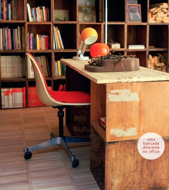 a modern rustic home office with a large shelving unit with books, a vintage wooden desk, a red chair, orange lamps