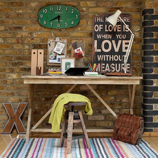 a rustic industrial home office done with an exposed brick wall, a wooden desk, a colorful striped rug and a clock and a sign