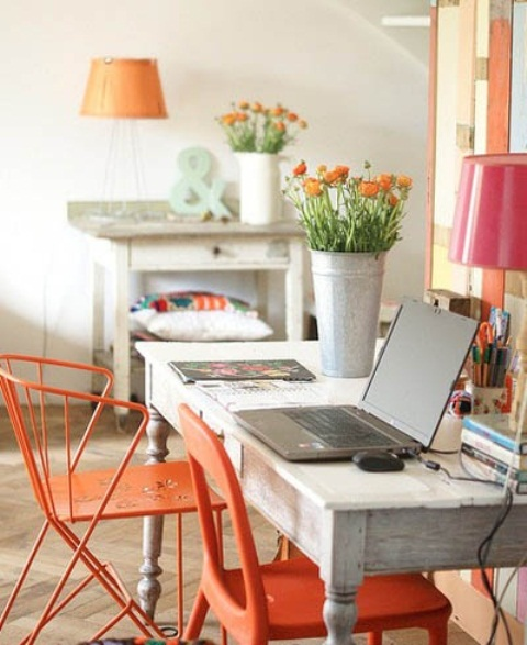 a bright rustic home office with wooden desks, bright orange and pink lamps and potted blooms and some artworks