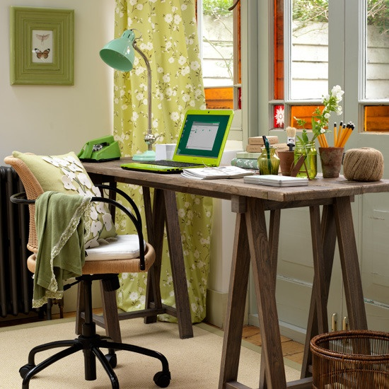 a modern and bright home office with colorful curtains, a wooden trestle desk and an industrial chair plus some blooms and lamps