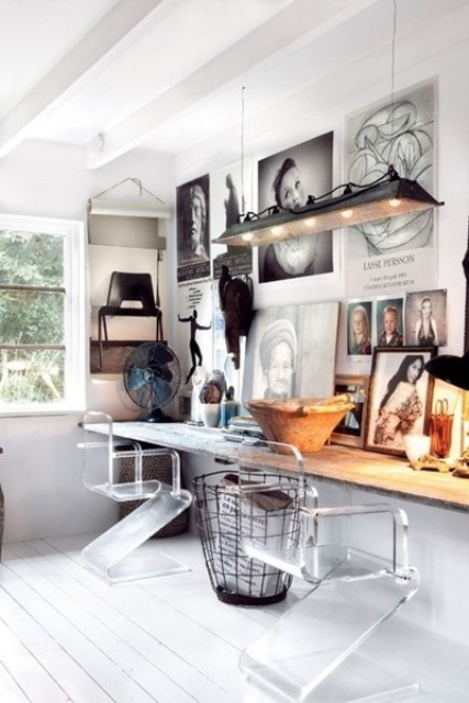 a white modern and rustic home office with a rough wood floating desk, an industrial pendant lamp, a gallery wall and ghost chairs
