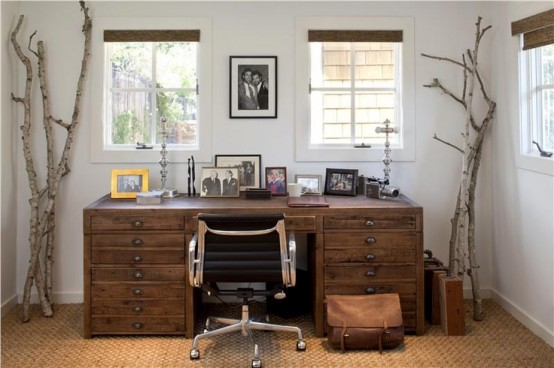 a neutral rustic home office with a wooden desk, tree branches, a jute rug, burlap shutters and a stylish mid-century modern chair