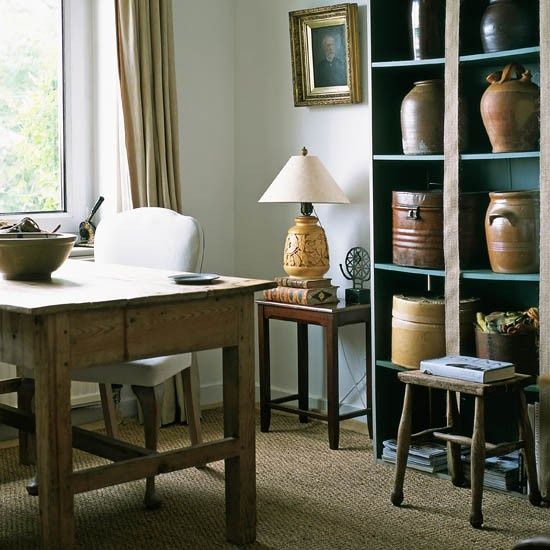 a refined rustic home office with a blue shelving unit, a rustic wooden desk, some lamps and artworks