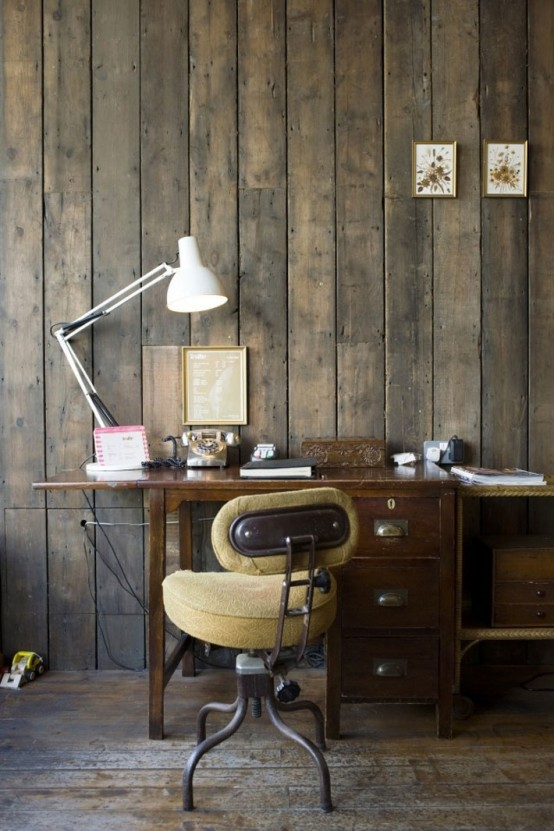 a rustic industrial home office with rough wooden walls, a vintage desk, a comfy chair and modern lamps and art