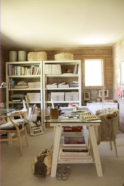 a cozy rustic home office in neutrals, with a white shelving unit and desk, a glass desk and wooden chairs