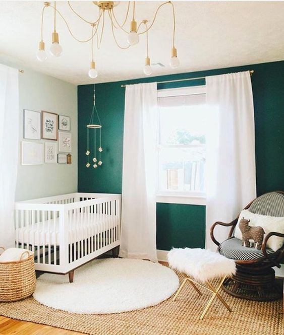 a bold modern nursery with a green accent wall, white and dark rattan furniture, layered rugs, a chandelier and a gallery wall