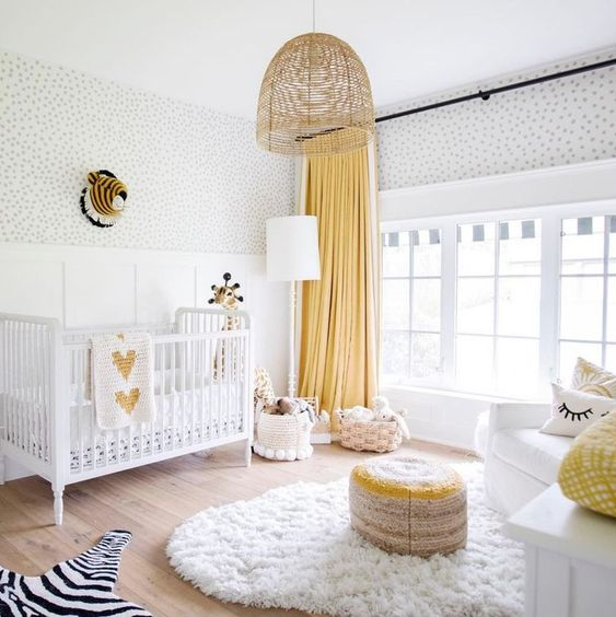 a bright nursery in white and yellow, with a fluffy rug, a colorful ottoman and baskets for storage
