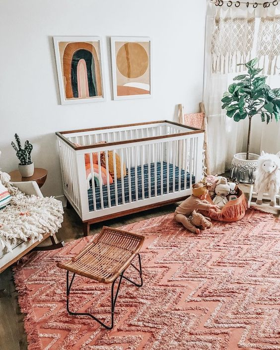 a boho nursery with a bright red ru, boho hangings, mid-century modern artworks and fluffy touches