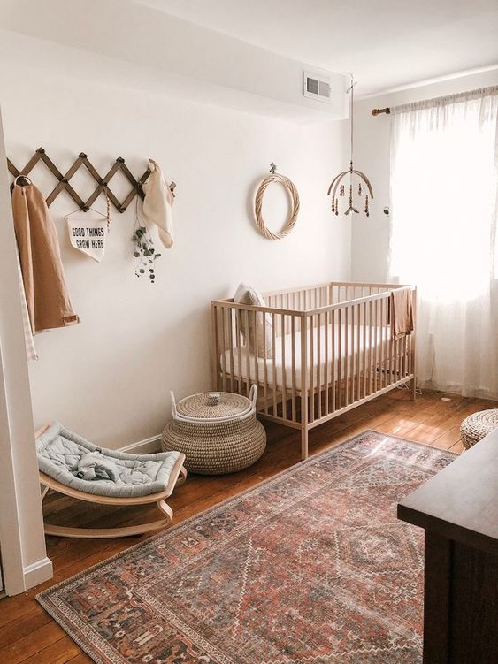 a boho gender neutral nursery with light stained furniture, a boho rug, a mobile and a littel rocker