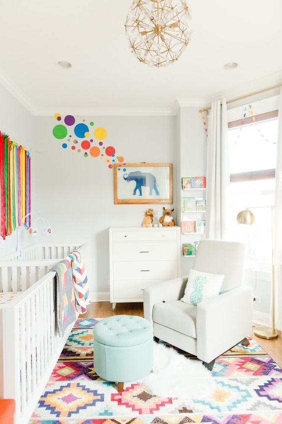 a colorful nursery with a bold wall, a colorful rug and textiles plus a wall hanging and white furniture as a backdrop