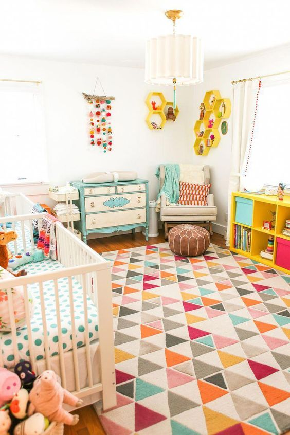 a colorful nrusery with a mint dresser, colorful bedding and textiles, bold honeycomb shelves on the wall