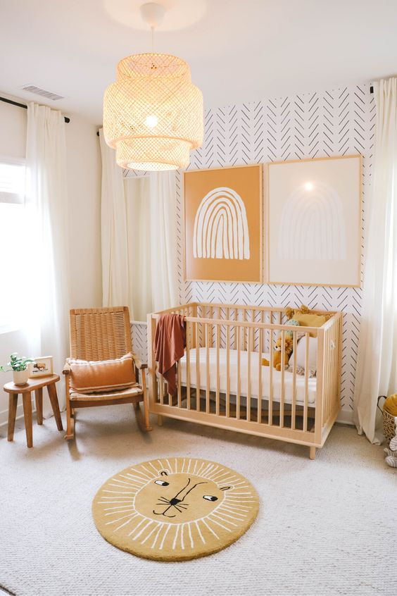 a cozy and warm-colored nursery with a printed wall, wooden furniture, a fun rug and bold art on the wall